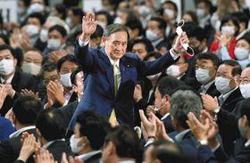 自民党の新総裁に選ばれ、両手を挙げて拍手に応える菅義偉官房長官(中央)=東京都内のホテルで