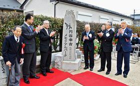 銘板除幕式に臨む安藤会長(右から2人目)、近藤会長(同3人目)。左は喜久造さん