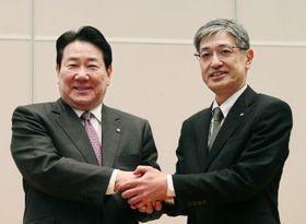 記者会見後、握手する日本航空の植木義晴社長(左)と赤坂祐二常務執行役員=24日午後、東京都品川区の日本航空本社