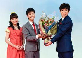 記者会見で横山だいすけさん(右)に花束を手渡す花田ゆういちろうさん(中央)。左は小野あつこさん=17日午後、東京・渋谷のNHK放送センター