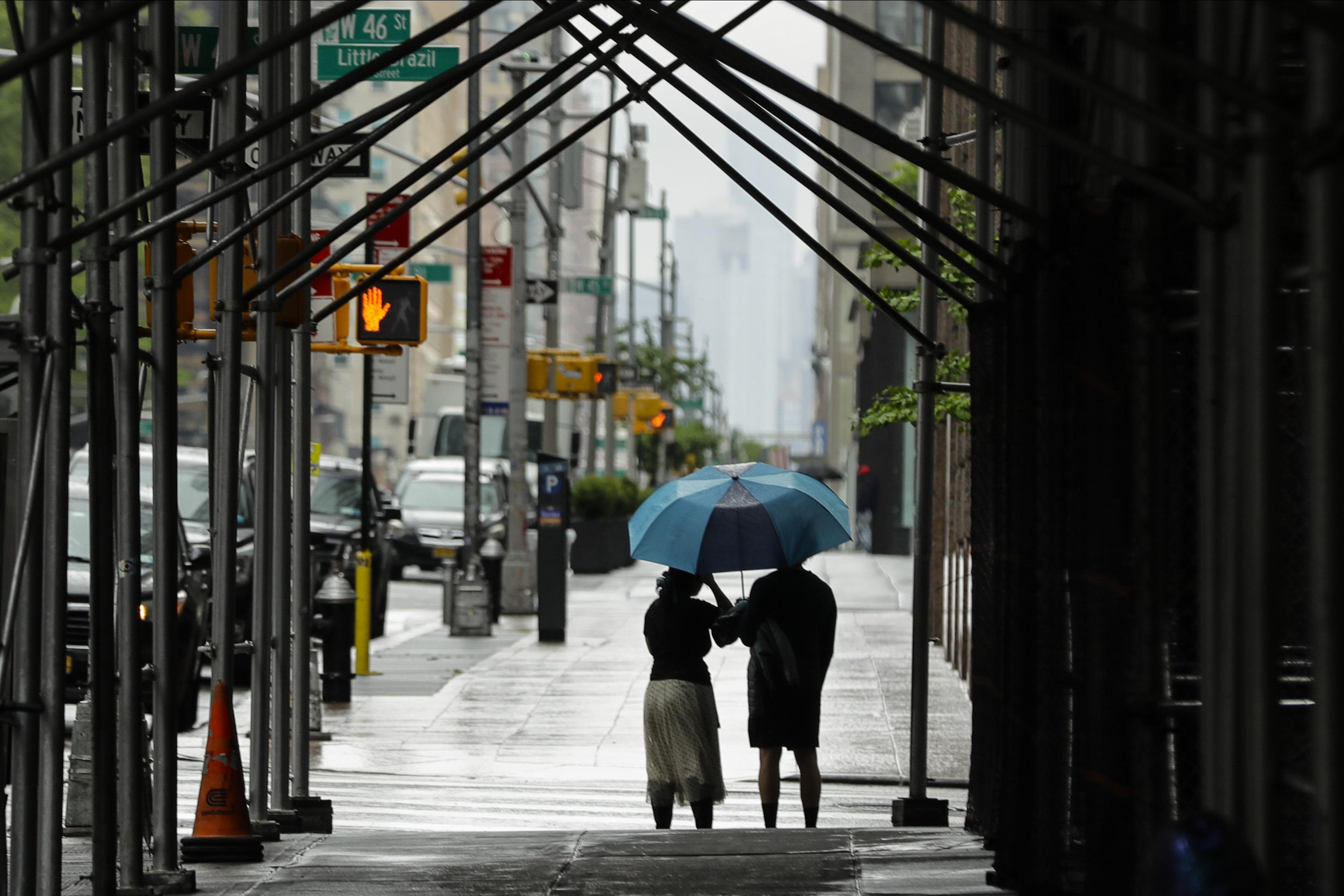 傘を差して歩く人々=23日、ニューヨーク(AP=共同)