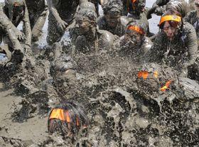 有明海の干潟で行われた「鹿島ガタリンピック」で泥まみれになる参加者=27日午後、佐賀県鹿島市