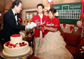 ケーキ入刀に臨む岡田哲弥さん(中)と夕季帆さん(右)