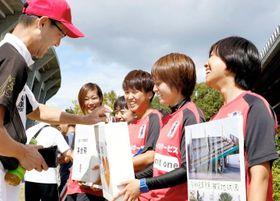 試合前に募金活動への協力を呼び掛ける愛媛FCレディースの選手ら=6日、県総合運動公園球技場
