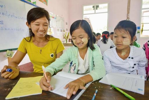 小学校で子どもたちにインタレー語のつづりを教えるクレー・モン(左)。「書き言葉が無ければ失われるものが多い。文字を使いこなせるようになれば、新しい歌や物語も紡ぎ出せる」という強い思いから次世代への教育を志した=19年8月、ミャンマー東部カヤ州(共同)