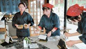 開店準備を進めるスタッフと、付け合わせの煮豆、漬物を手にする松下美智子さん(右から3人目)=小矢部市埴生で