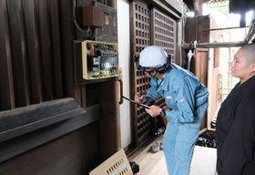 革堂行願寺の本堂の配電盤を点検する京都電業協会の会員(左)=京都市中京区