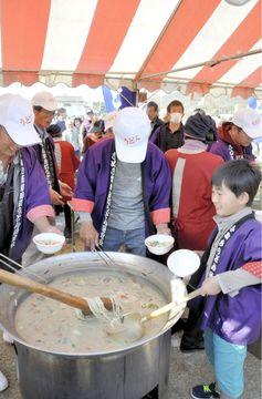 熱々のドジョウ汁を盛りつける参加チームのメンバー=香川県さぬき市造田野間田