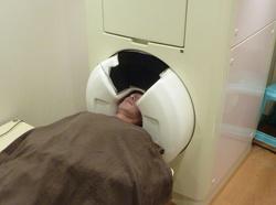 脳磁計のセンサー部分に頭を入れて磁場を計測する脳磁図検査=仙台市