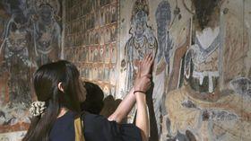 再現された中国・敦煌の莫高窟の壁画に触れる来場者=13日、松江市の島根県立美術館