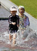 夏を思わせる陽気の中、水場で遊ぶ子どもたち=鹿児島市の鹿児島ふれあいスポーツランド