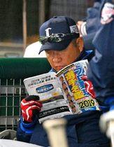 試合中、選手名鑑を読む西武・辻監督