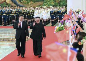 北京の人民大会堂で歓迎式典に臨む中国の習近平国家主席(左)と北朝鮮の金正恩朝鮮労働党委員長=19日(新華社=共同)