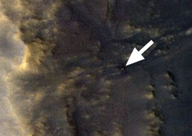 NASAが無人探査車オポチュニティーを捉えたとして発表した画像。矢印の先に白い点として写っているという(NASA提供)