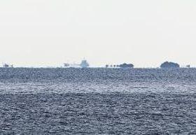 写真【光の屈折により、船や島が浮き上がったように見える浮島現象(21日午前8時45分、和歌山県串本町姫で)】