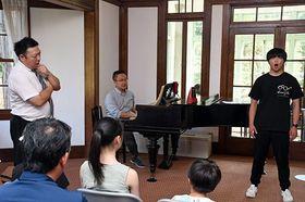 三浦代表(左)、櫻田さん(中)の指導を受けながら発声トレーニングを行う参加者