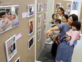 「子どもたちの成長を知ってほしい」と写真を紹介する漆畑さん(手前)たち