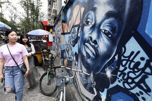 若者らが集まる通りの壁に描かれた米国人ラッパーとみられる絵。当局の規制でタトゥーやピアスをしたラッパーのテレビ番組起用は規制されたが、若者にはファッションも人気だ=19年5月、中国・成都(共同)
