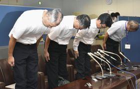 記者会見で頭を下げる東邦航空運航部の有吉衛部長(左端)と群馬県の職員=16日午後、群馬県庁