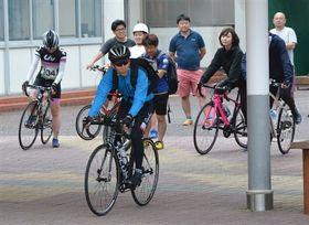自転車のペダルをこいで出発する参加者=牧之原市の旧片浜小