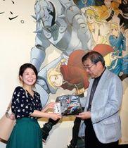 来場1万人目の山田さん(左)に記念品を手渡す岡館長=神戸ゆかりの美術館