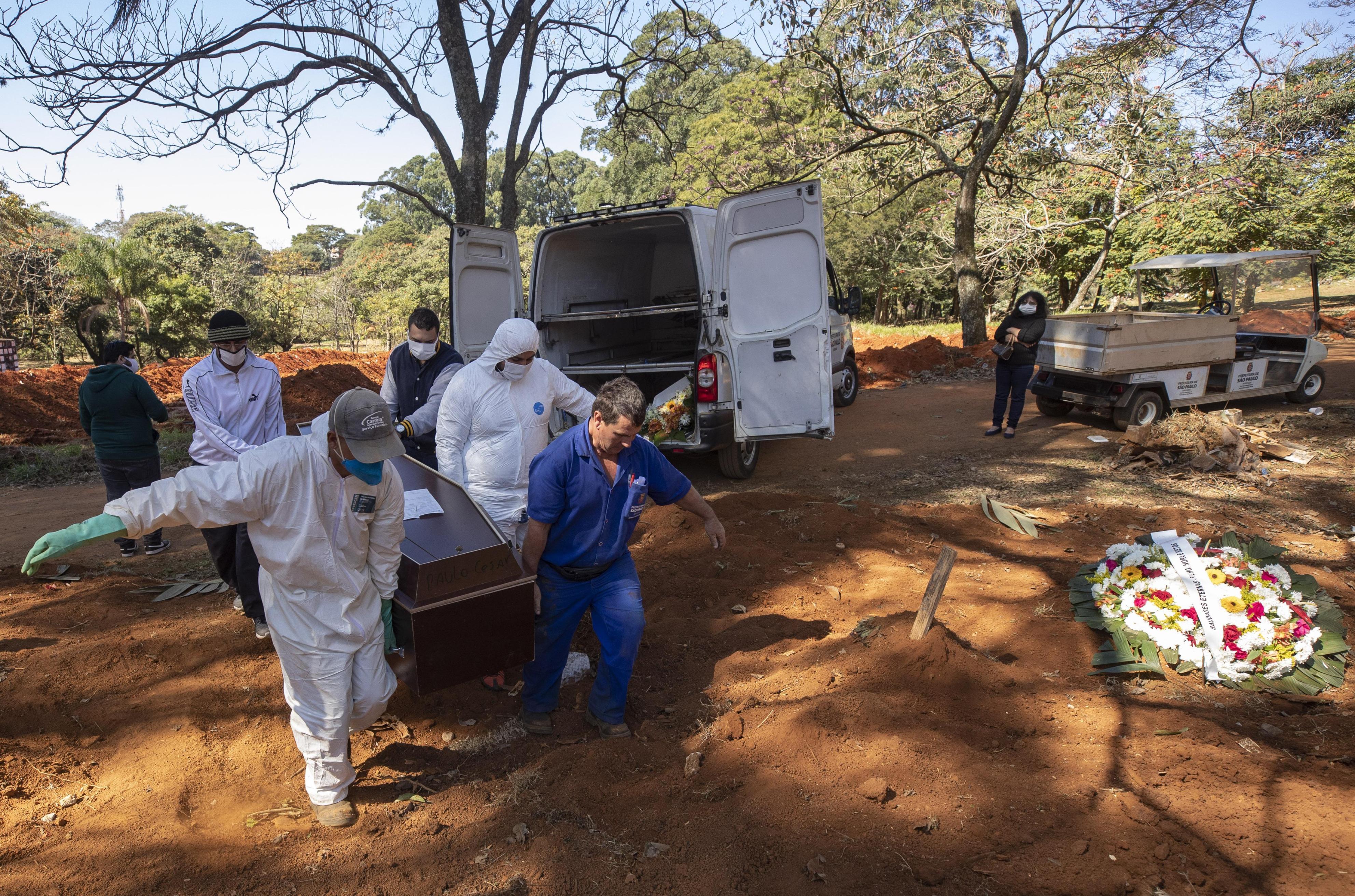 ブラジル・サンパウロの墓地で、防護服を着て新型コロナ感染死者の棺おけを運ぶ人たち=5月28日(AP=共同)