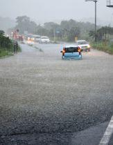大雨で県道が冠水し立ち往生する車=屋久島町小瀬田