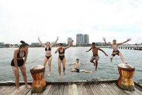 15日、オーストラリア南東部ビクトリア州メルボルンで海に飛び込む若者たち(ゲッティ=共同)