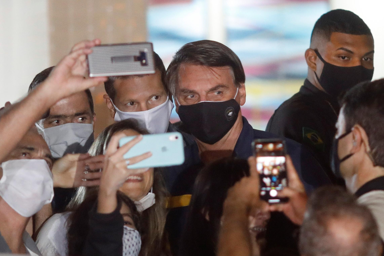 支持者と写真撮影するブラジルのボルソナロ大統領=23日、ブラジリア(ロイター=共同)