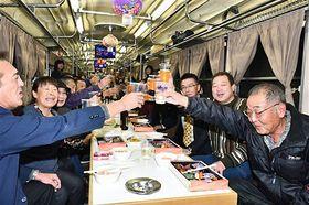 「乾杯!」と一斉にグラスを合わせる乗客たち=6日午後6時36分、平川市