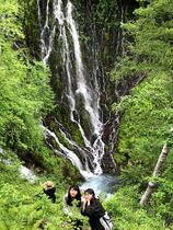 新しく始まったツアーで布引滝を訪れた台湾の学生ら=高山市丹生川町、乗鞍山麓五色ケ原の森