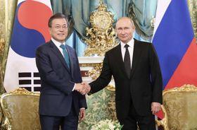 22日、モスクワでの首脳会談で、握手する韓国の文在寅大統領(左)とロシアのプーチン大統領(聯合=共同)
