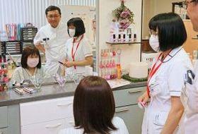 柿木康孝医師らと相談しながら、鏡を見てウィッグを合わせる桜井さん(手前)。アピアランスケア室は入院患者の憩いの場でもある(舘山国敏撮影)