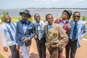 ブラザビルで、サプール仲間と集うパッシャンス・ムタラ(中央左)。後方のコンゴ川の対岸は隣国、コンゴ民主共和国の首都キンシャサだ(撮影・中野智明、共同)
