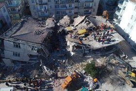 地震で倒壊した建物で続く捜索活動=25日、トルコ東部エラズー県(ゲッティ=共同)