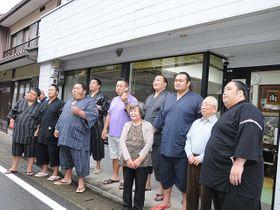 住宅や店舗の前で、住民と記念撮影をする力士たち=下呂市金山町金山