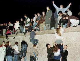 1989年11月、東ドイツ政府の国境開放後、東側からベルリンの壁をよじ登る市民たち(ロイター=共同)
