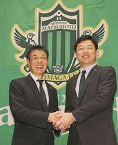 就任会見で松本山雅運営会社の神田文之社長(右)と握手する布啓一郎新監督=15日、松本市内のホテル