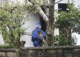 住宅火災現場を調べる捜査員=27日午後、福岡県田川市