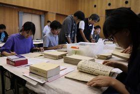 旧島原藩に由来する史料の調書を作成する大学生ら=島原図書館