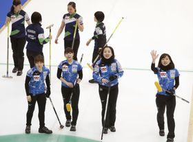 北海道銀行(奥)に勝って決勝進出を決め、声援に応えるロコ・ソラーレの4選手=どうぎんカーリングスタジアム
