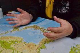 日本海の地図を前に、北朝鮮漁業の実態を説明する脱北者の男性=6日、ソウル市内