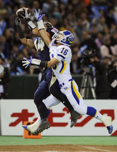 パスを奪い合うオービックのDB藤本(左)と関学大のWR和田=2012年、東京ドーム