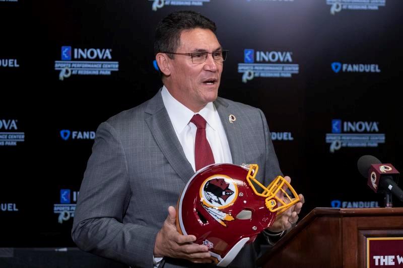 レッドスキンズのヘルメットを手にして就任の記者会見に臨むロン・リベラ新ヘッドコーチ(AP=共同)