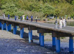 四万十川に架かる沈下橋を走る聖火ランナー=19日午後、高知県四万十市