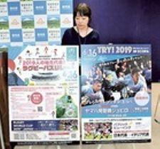 ボードを掲げて6月16日に開催する「ラグビーパスリレー」などをPRする県職員=21日、県庁