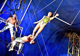 空中ブランコで華麗に宙を舞うパフォーマー=14日午後、郡山市・ショッピングモールフェスタ大テント