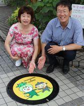 【「ちゃちゃもとマンホーくん」のデザインマンホールを披露する竹上市長(右)と村上さん=松阪市本町で】