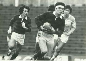 早稲田大3年時に、筑波大との対抗戦でプレーする津布久さん(中央)。この試合中に左膝靱帯断裂の大けがを負った=1981年11月、東京・秩父宮ラグビー場(本人提供)