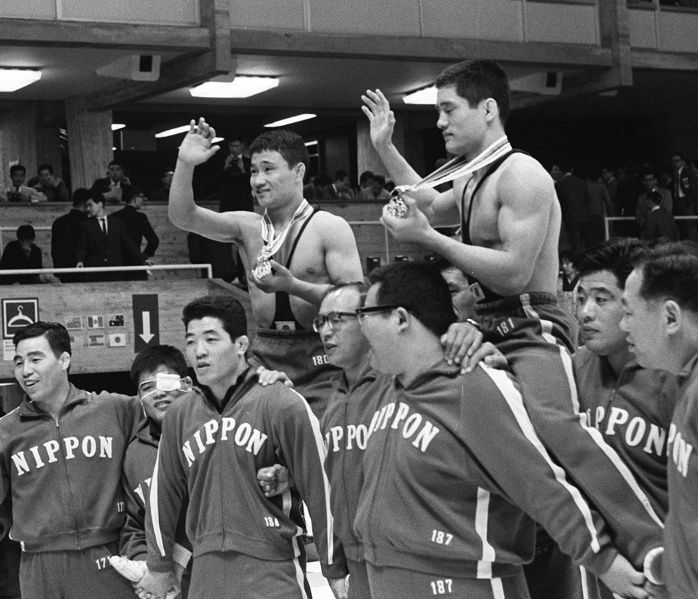 1964年10月19日、レスリング・グレコローマンで優勝した市口政光(右)と花原勉の両選手。同僚に担がれ場内を1周する
